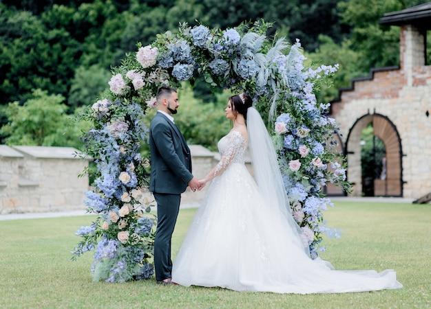 Noivo e noiva estão juntos em frente ao arco decorado com hortênsia azul, de mãos dadas, cerimônia de casamento, votos de casamento