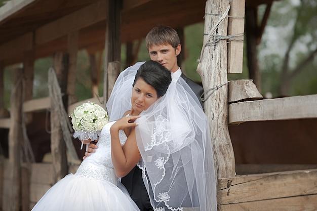 Noivo e noiva estão perto do abrigo de cavalo