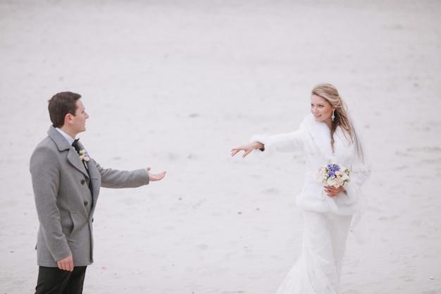 Noivo e noiva estendendo os braços