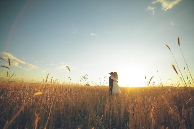 Noivo e noiva feliz se abraçam no parque ao pôr do sol.