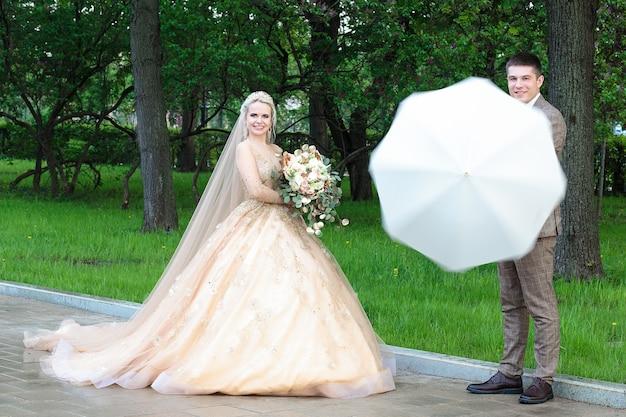 Noivo e noiva felizes com um guarda-chuva branco na chuva, no verão no parque. casamento ao ar livre.