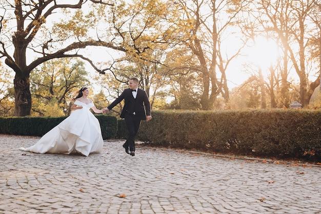 Noivo e noiva felizes correndo alegremente juntos por um caminho no dia do casamento