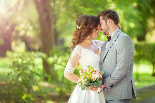 Noivo e noiva felizes em um parque no dia do casamento Foto Premium