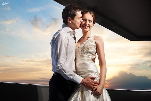 Noivo e noiva felizes no casamento caminham em frente ao pôr do sol na cidade