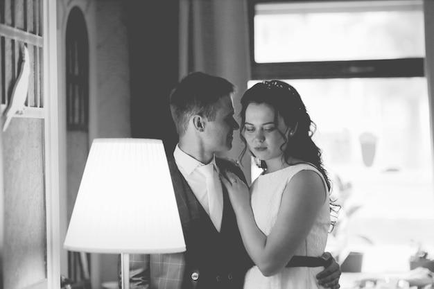Noivo e noiva felizes se abraçam.