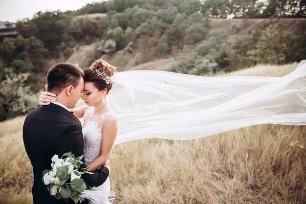 Noivo e noiva posando do lado de fora