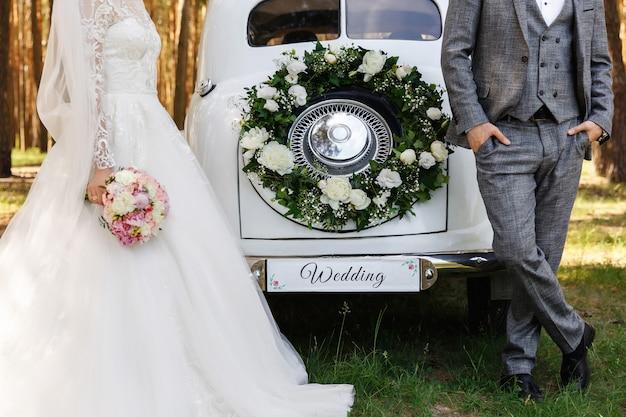 Noivo e noiva posando perto de carro branco recém casado com inscrição '' casamento ''