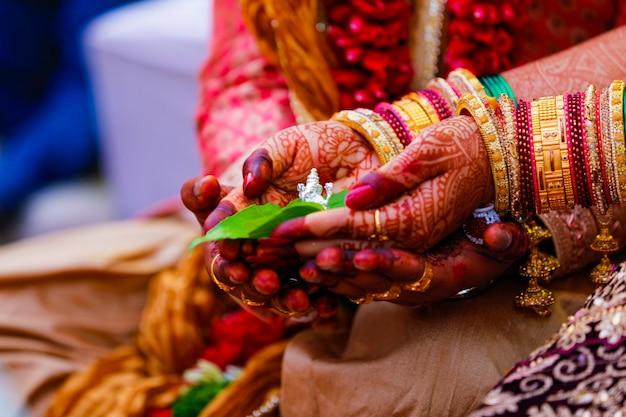 Noivo e noiva segurando uma folha verde e a escultura do senhor ganesha na mão