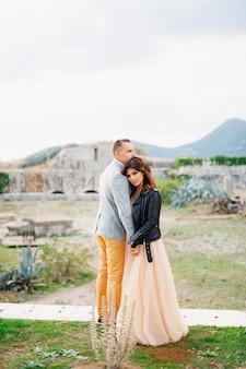 Noivo e noiva sérios em um vestido de noiva em tons pastéis e uma jaqueta de couro preta