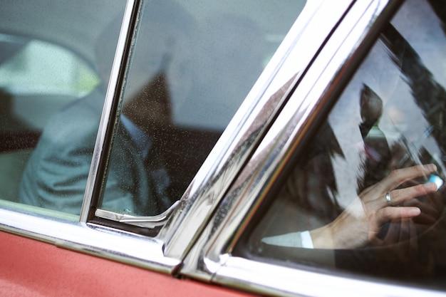 Noivo e uma noiva sentados em um carro vintage vermelho