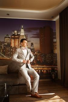 Noivo elegante aguarda a noiva em um apartamento elegante