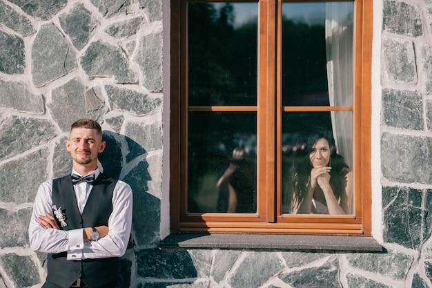 Noivo elegante em frente a parede com sua noiva olhando para ele pela janela