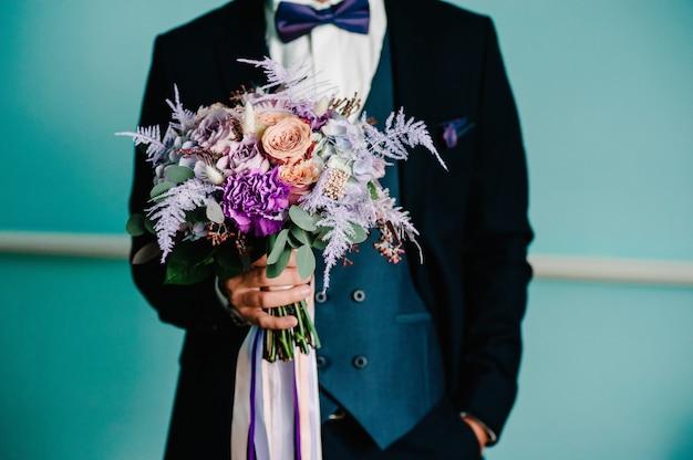 Noivo elegante está segurando um buquê de noiva. buquê de casamento nas mãos do homem.