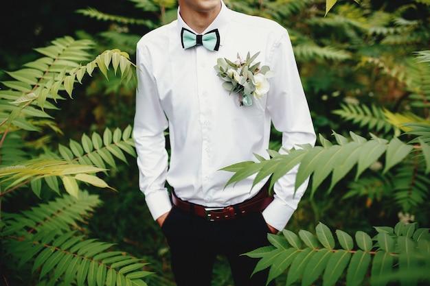 Noivo em camisa branca com gravata borboleta e flor na lapela. mãos nos bolsos.