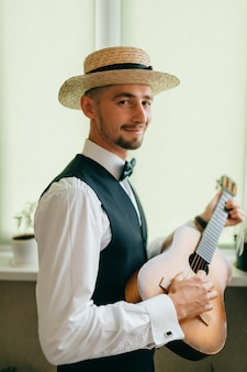 Noivo em roupas de estilo country, posando com guitarra