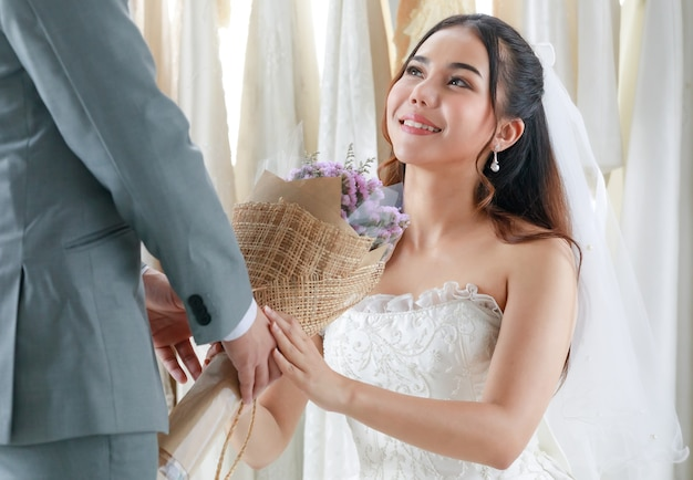 Noivo em terno formal cinza dar flores de bougue de casamento para noiva linda.