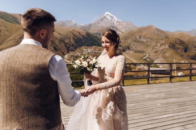 Noivo em terno moderno e noiva com vestido de vestido rosa encantador no terasse com excelente vista para a montanha na geórgia