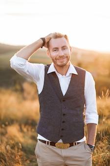 Noivo em um elegante terno andando no campo ao pôr do sol