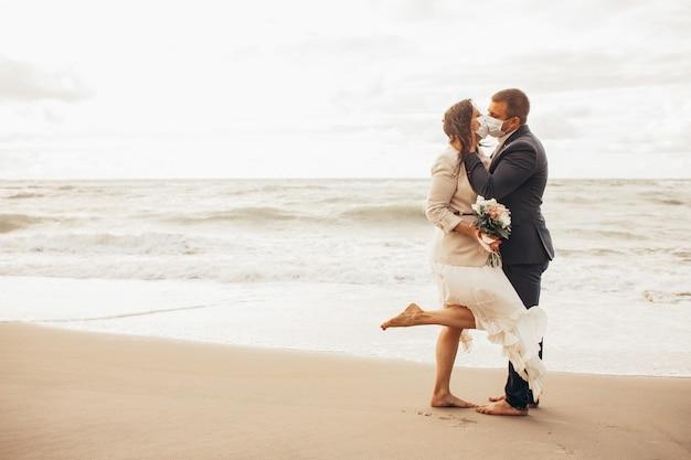 Noivo em um terno chique e uma noiva linda em um vestido de noiva andando na praia. recém-casados beijos em máscaras médicas protetoras. toned