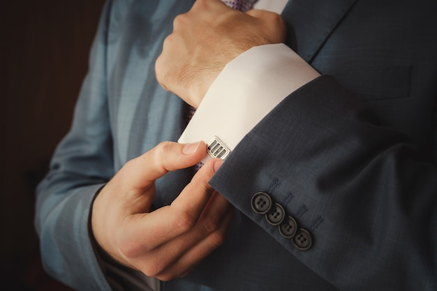 Noivo está colocando em botões de punho como ele se veste com roupa formal close-up