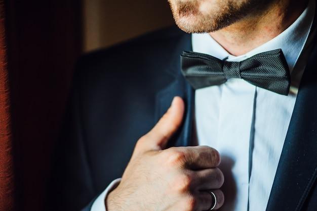 Noivo está de mãos dadas na gravata borboleta, terno de casamento