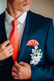 Noivo está segurando as mãos na gravata, terno de casamento