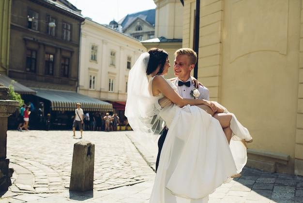 Noivo feliz carregando a noiva em seus braços