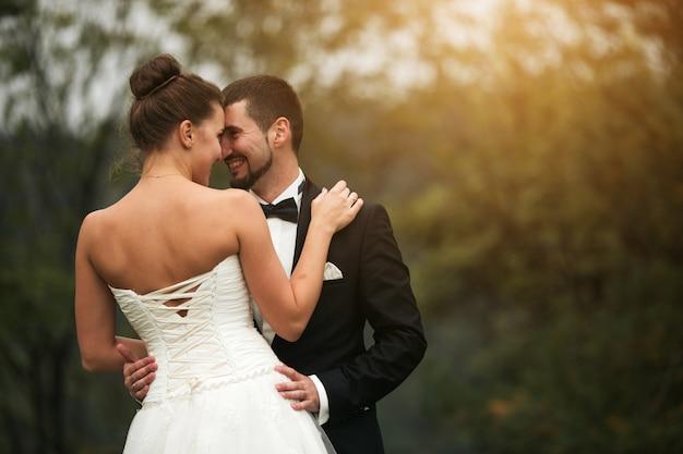 Noivo feliz com mãos na cintura da noiva