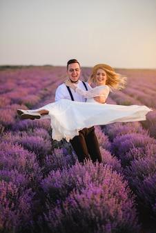 Noivo feliz segurando a noiva nos braços em um campo de lavanda florescendo ao pôr do sol
