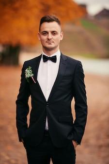 Noivo jovem elegante em um terno preto