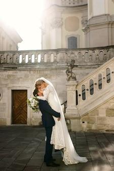 Noivo levanta a noiva e ela o abraça antes de escadas brancas para a igreja velha
