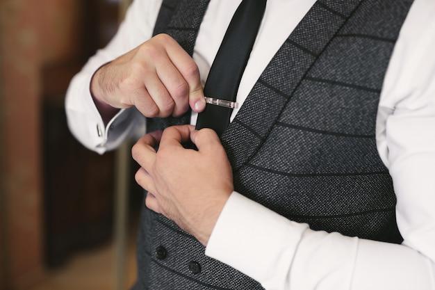 Noivo lindo elegante se preparando a manhã no quarto de hotel, segurando o clipe na gravata