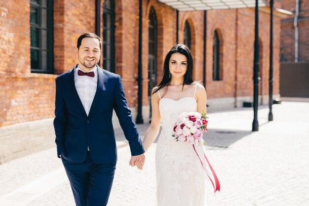 Noivo masculino barbudo veste terno preto formal mantém a mão de sua noiva