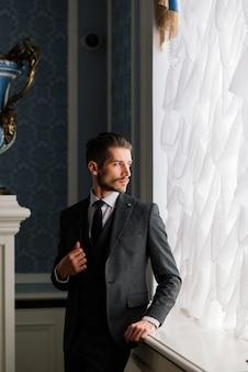 Noivo no dia do casamento sorrindo e esperando a noiva no corredor do hotel. homem rico elegante em traje e gravata borboleta.
