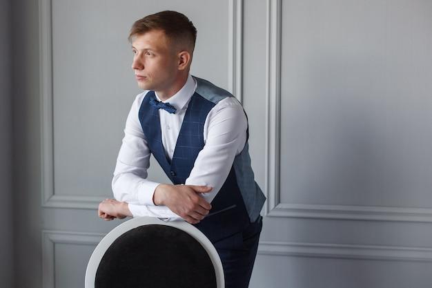 Noivo no quarto de hotel em uma camisa e calça em uma cadeira