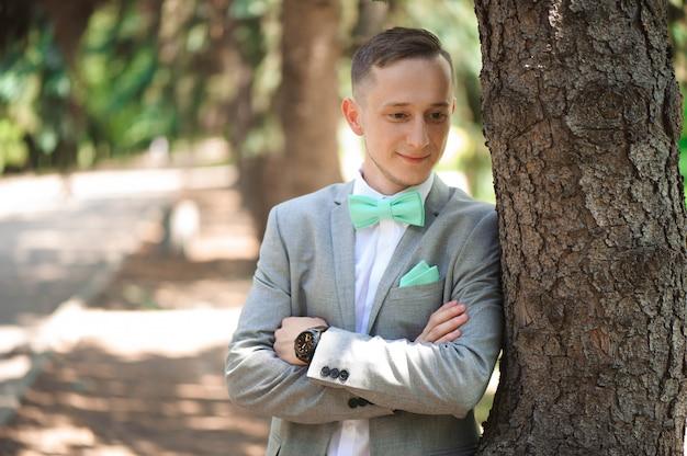 Noivo no smoking do casamento que sorri e que espera a noiva. noivo rico no dia do casamento. noivo elegante em traje e gravata borboleta.