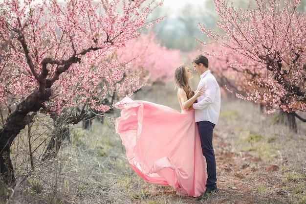 Noivo romântico beijando a noiva na testa em pé contra a parede coberta com flores cor de rosa