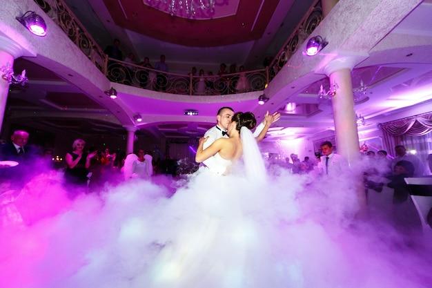 Noivo se inclina a noiva dançando sobre a fumaça