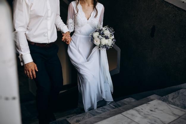 Noivo segura a mão da noiva enquanto sobem