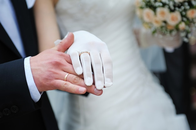 Noivo segura a mão da noiva na cerimônia de casamento