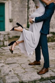 Noivo segura a noiva nos braços enquanto está de pé nas pedras do pavimento no pátio da casa