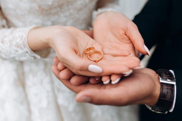 Noivo segura as mãos da noiva, onde estão dois anéis de casamento