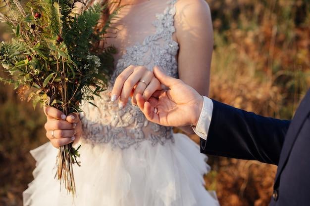 Noivo segura na mão a mão da noiva