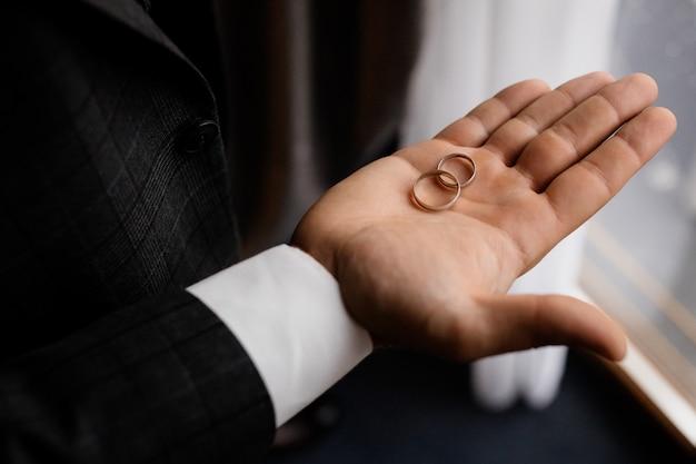Noivo segura na palma da mão dois anéis de casamento