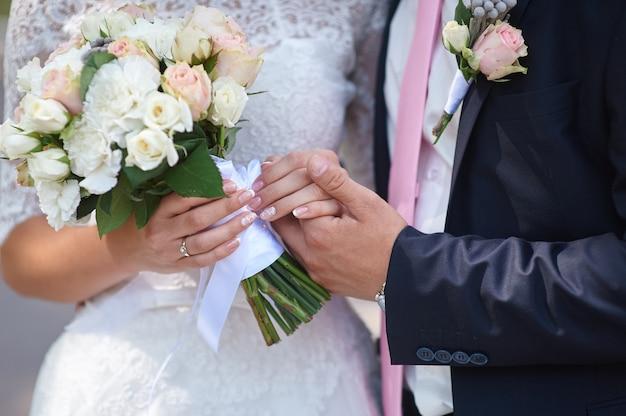 Noivo segura sua mão de noivas e um buquê de casamento