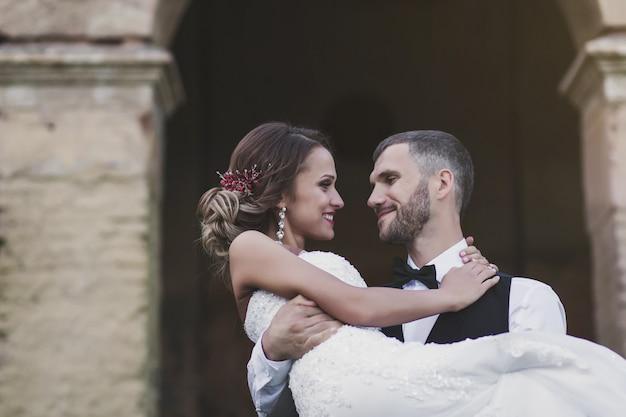 Noivo segura uma linda noiva nos braços