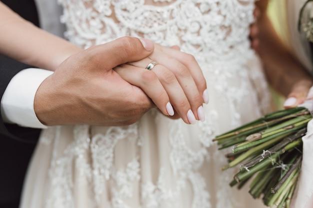 Noivo segura uma noiva para a mão