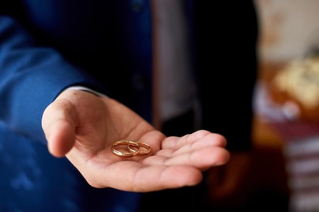 Noivo segurando alianças na palma da mão