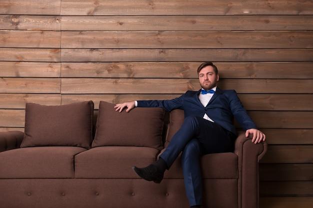 Noivo sério de terno e gravata borboleta sentado no sofá na sala de madeira