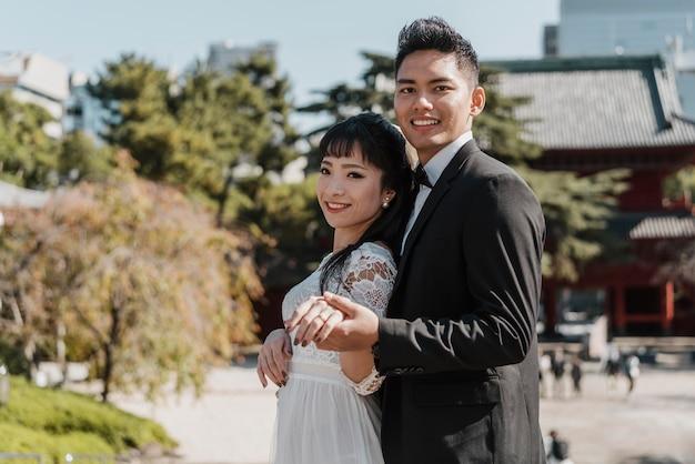 Noivo sorridente e noiva posando juntos ao ar livre